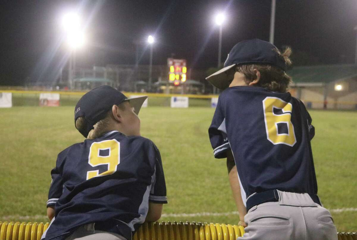 Class A Thunder players Jaxson Nettles (9) and Walker Long (6) watch a little bit of a Triple A contest as they share some fence time together Thursday night. The duo will be playing in next week's Class A title game.