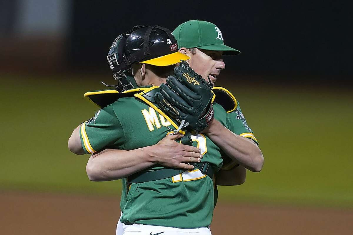 Oakland Athletics catcher Sean Murphy, foreground, celebrates with pitcher Chris Bassitt after the Athletics defeated the Los Angeles Angels in a baseball game in Oakland, Calif., Thursday, May 27, 2021. (AP Photo/Jeff Chiu)