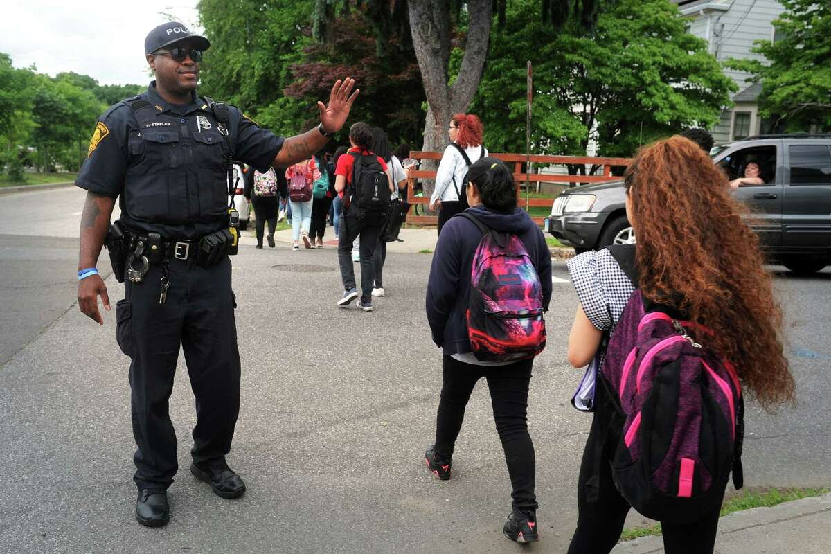 Bridgeport Police Officer John Staples, a Schools Resource Officer (SRO), greets students following as the leave Central High School at the end of their school day in Bridgeport, Conn. June 15, 2018.