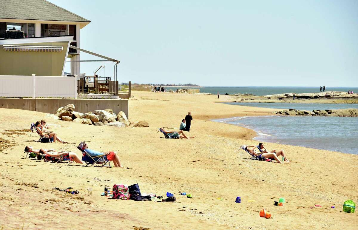 People enjoy the warmth and sunshine at the Surf Club town beach in Madison during the COVID-19 pandemic. Last year, the town limited the beach to 50 percent capacity, a restriction that is being lifted this summer.