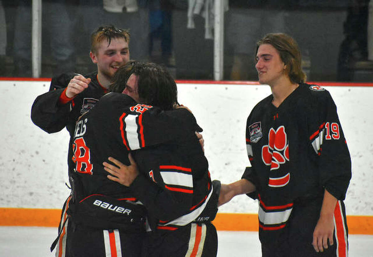 Members of the Edwardsville ice hockey team celebrate after winning the MVCHA championship.
