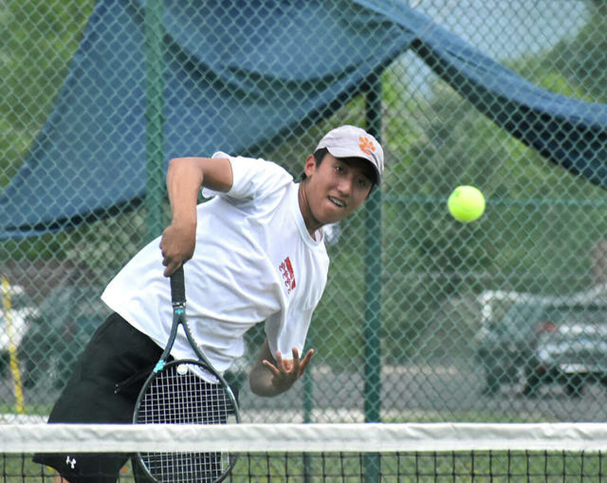 Edwardsville's Adrian Norcio slams down a shot at the net during his No. 3 doubles final match against Belleville East on Thursday in O'Fallon.