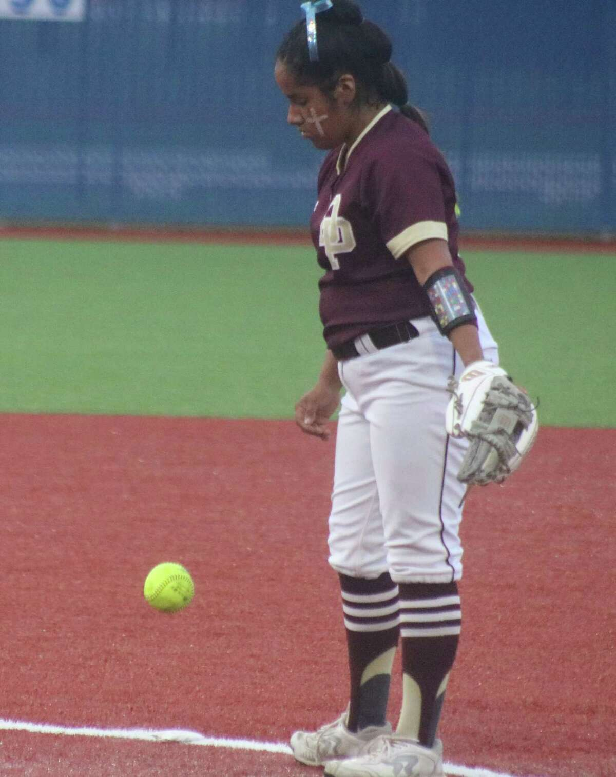 Hanna Benavides bounces a softball on the turf during her pitching assignment against Ridge Point. Unbeaten in the playoffs, she'll try and do her part to get the team past Clear Springs this weekend.