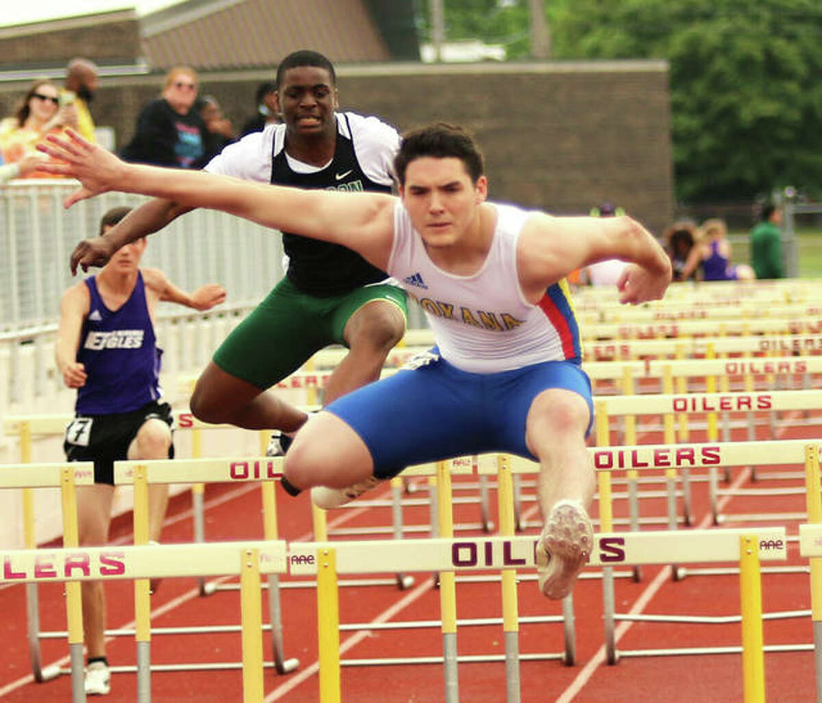 Roxana's Aidan Flener (front) clears a hurdle at the Madison County Meet on May 17 in Wood River. On Thursday at the SCC Meet in Pana, Flener was second in the 100 hurdles and third in the 300 hurdles.
