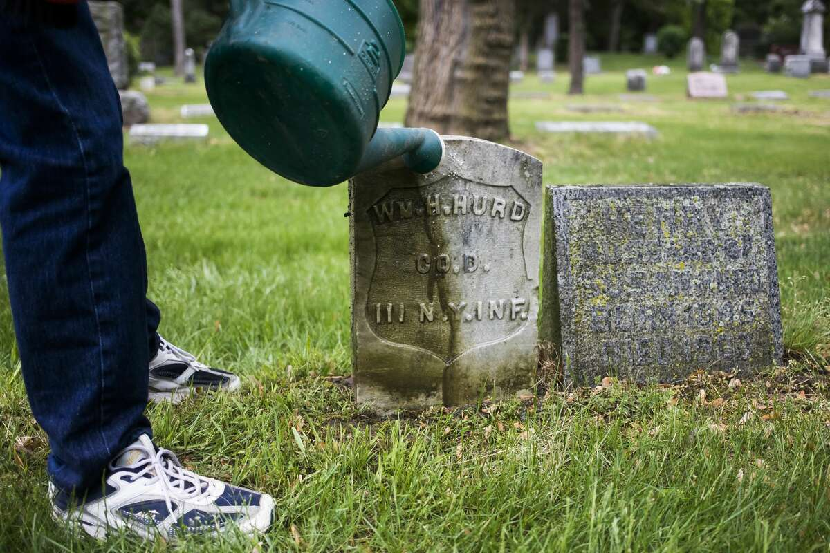 Floyd Andrick of the Midland County Historical Society begins the process of cleaning the headstone of civil war veteran William H. Hurd Thursday, May 27, 2021 in the Midland Municipal Cemetery. The headstone on the left was previously cleaned by Andrick. (Katy Kildee/kkildee@mdn.net)