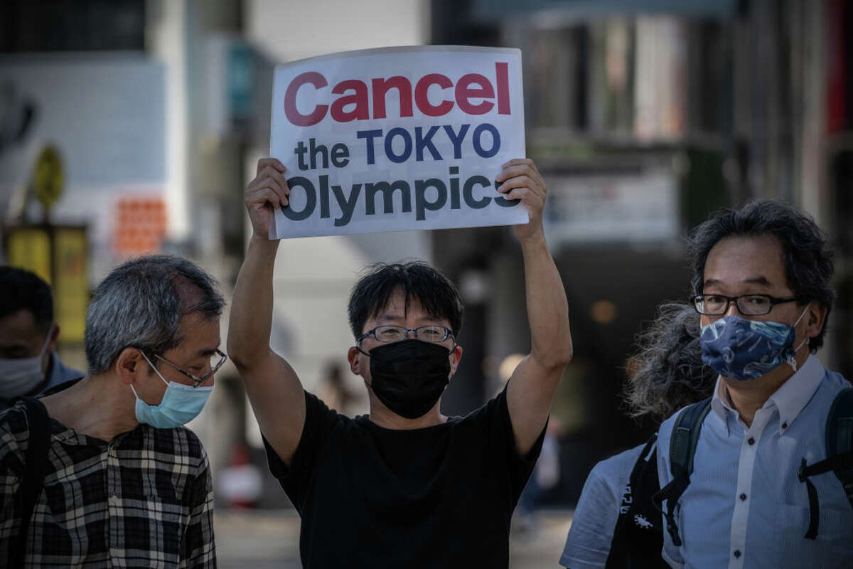 On May 23, 2021, a protester in Tokyo holds a placard during a demonstration against the forthcoming Tokyo Olympic Games.
