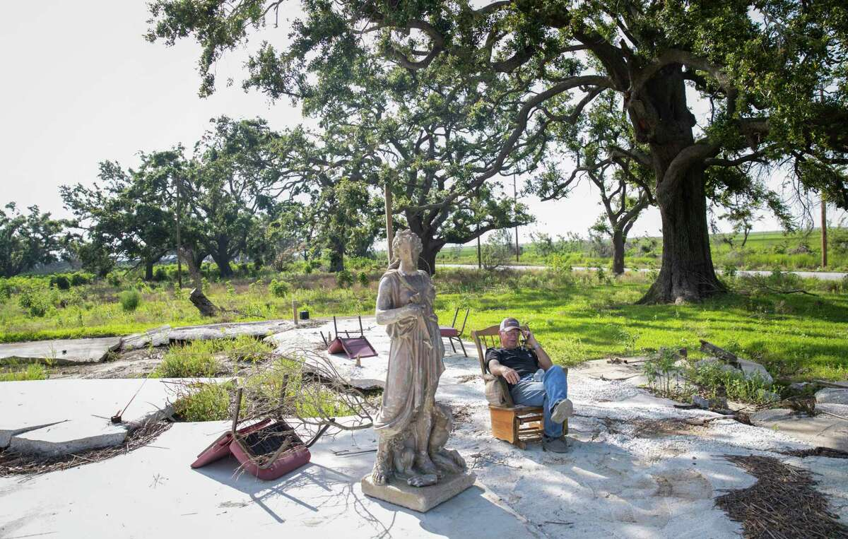 """David Ball talks on the phone as he sits on a slab that once held his home Thursday, May 27, 2021, near Grand Chenier, La. """"This is still my place,"""" he said. """"When I was born on this earth, it wasn't mine, it's mine now."""""""