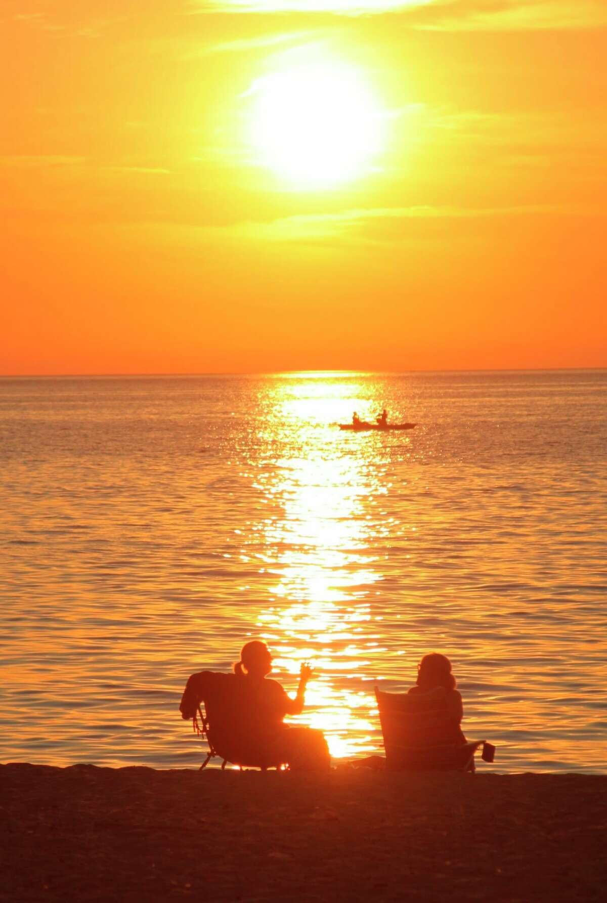 Taking in a sunset on the shores of Lake Michigan is a wonderful way to punctuate a summer night. (File photo)