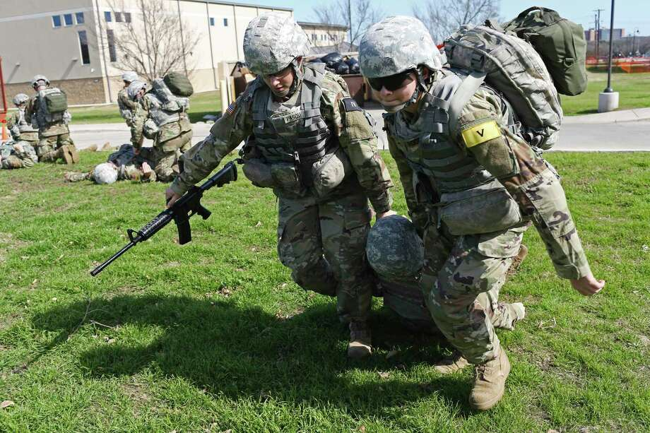 U.S. Army medic trainees at Fort Sam Houston in 2017 included Pvt. Andrea Pasquarelli, left, 19, of Keen, New Hampshire and Pvt. Lillias Rodriguez, 19, of San Antonio, right, carrying Pfc. Amanda Woodworth, 19, of Kendall, Wisconsin. With the pandemic easing, medic trainees will be allowed off the post this weekend to visit San Antonio — but not its bars — for the first time in 14 months. Photo: JERRY LARA /San Antonio Express-News / © 2017 San Antonio Express-News
