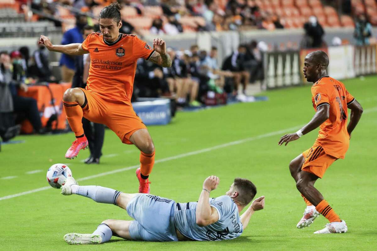 Dynamo defender Zarek Valentin, leaping over a Sporting KC defender, delayed a call-up to Puerto Rican national team to help Houston in its match against Kansas City this week.