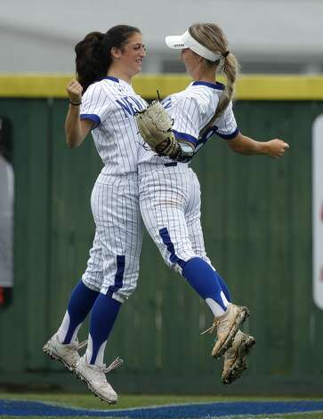 New Caney left fielder Katie Coogler (15) chest bumps right fielder Corigan Beaird (88) before the first inning of a District 20-5A high school softball game, Tuesday, April 13, 2021, in New Caney. Photo: Jason Fochtman/Staff Photographer / 2021 © Houston Chronicle