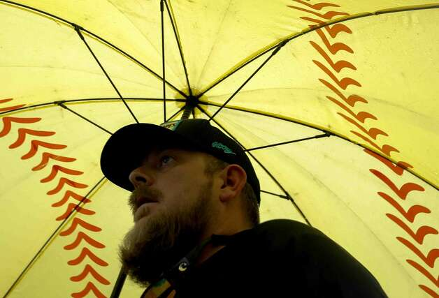 Andy Vaughn makes use of his softball-themed umbrella as rain continues to fall during a District 13-6A high school softball game at Willis High School, Friday, April 16, 2021, in Willis. Photo: Jason Fochtman/Staff Photographer / 2021 © Houston Chronicle
