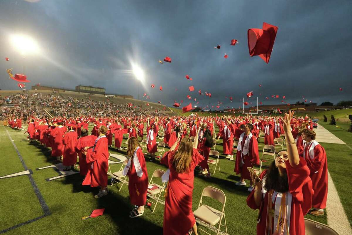 Members of the Memorial High School class of 2021 toss their caps in the air following the conclusion of the graduation ceremony at Darrell Tully Stadium on May 21