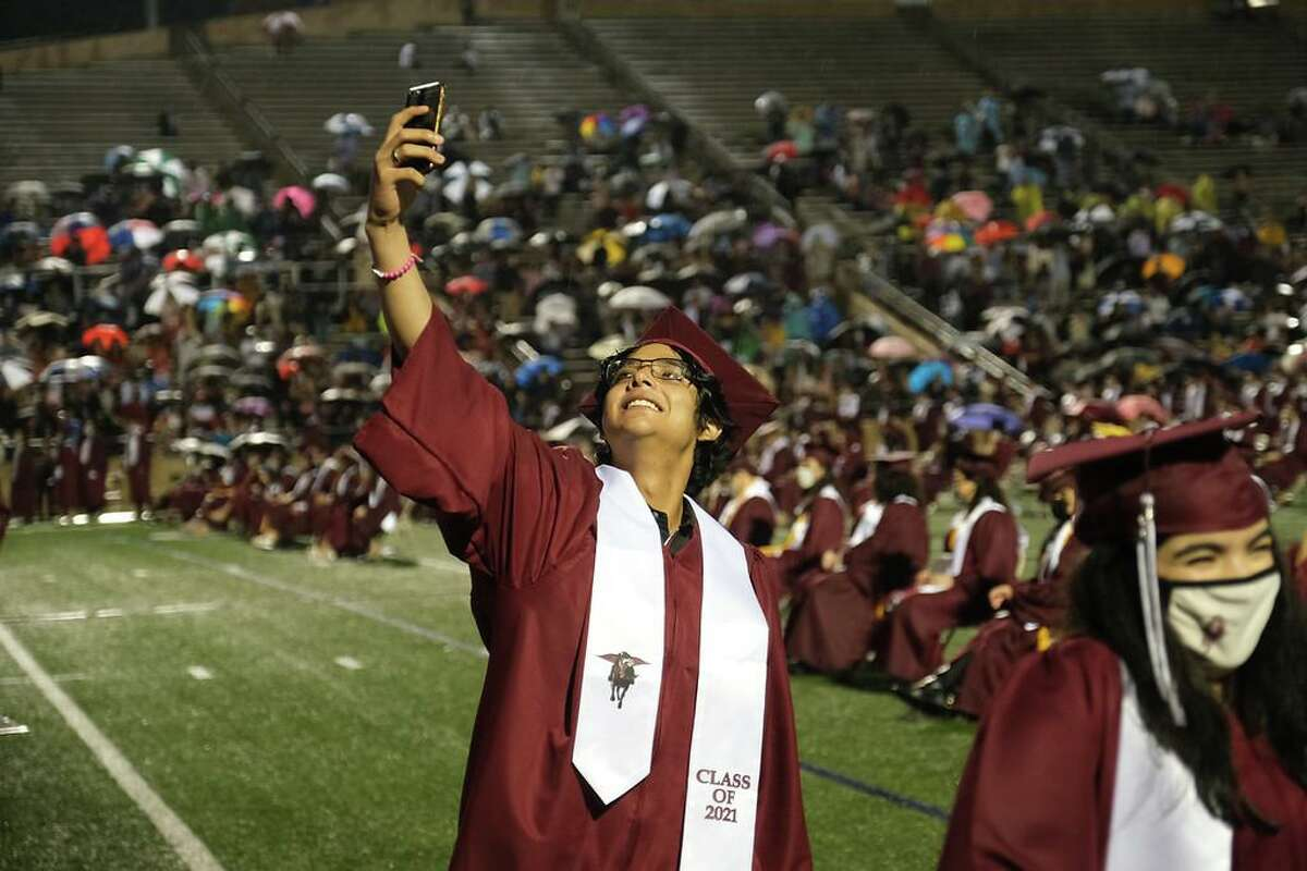A member of the Northbrook class of 2021 takes a selfie after crossing the stage during the graduation ceremony at Darrell Tully Stadium on May 22