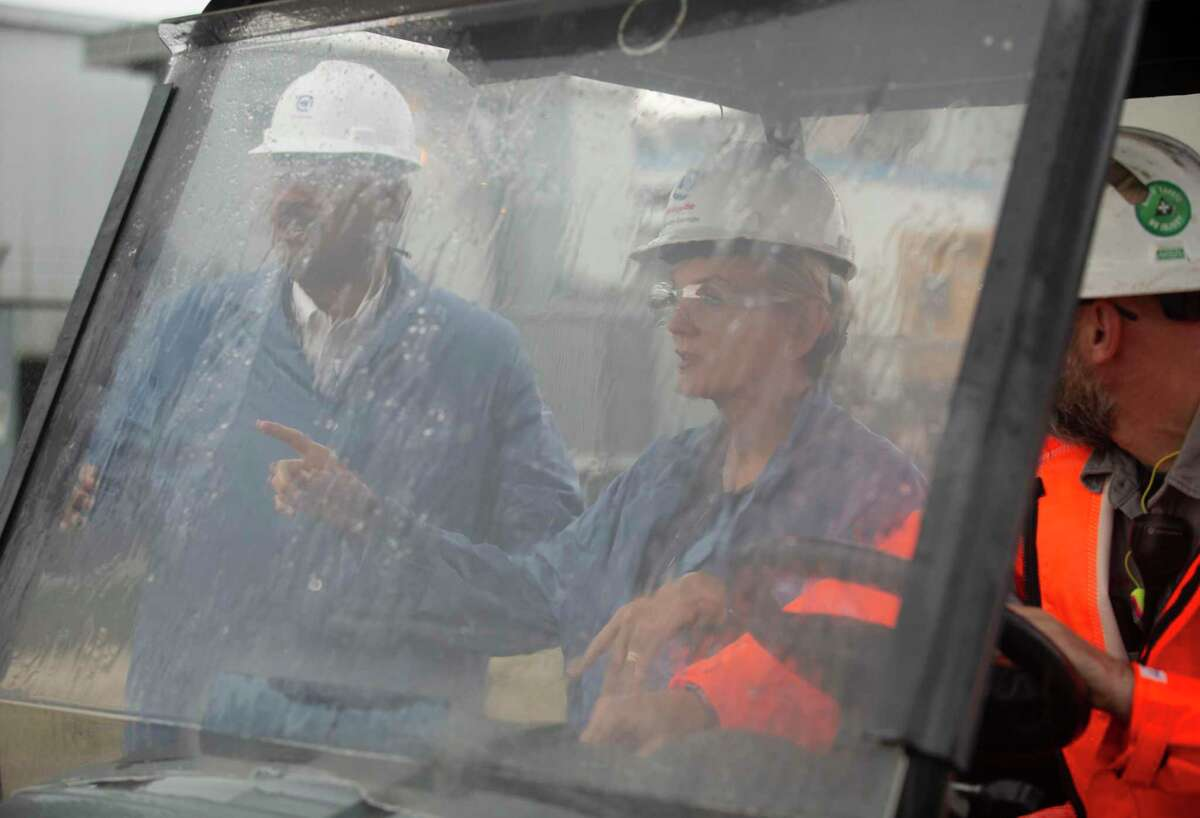 U.S. Secretary of Energy Jennifer M. Granholm, center, gets into a utility vehicle to start a tour in pouring rain at a Air Liquide hydrogen facility Friday, May 28, 2021, in La Porte.