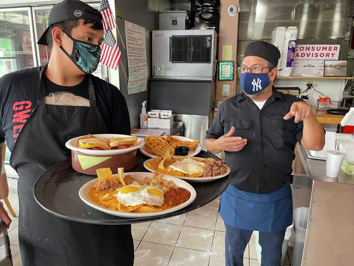 Sergio Calderon speaks with an employee at his restaurant, Panchos & Gringos. The pandemic year has taken a toll, and now the challenge is to hire employees.