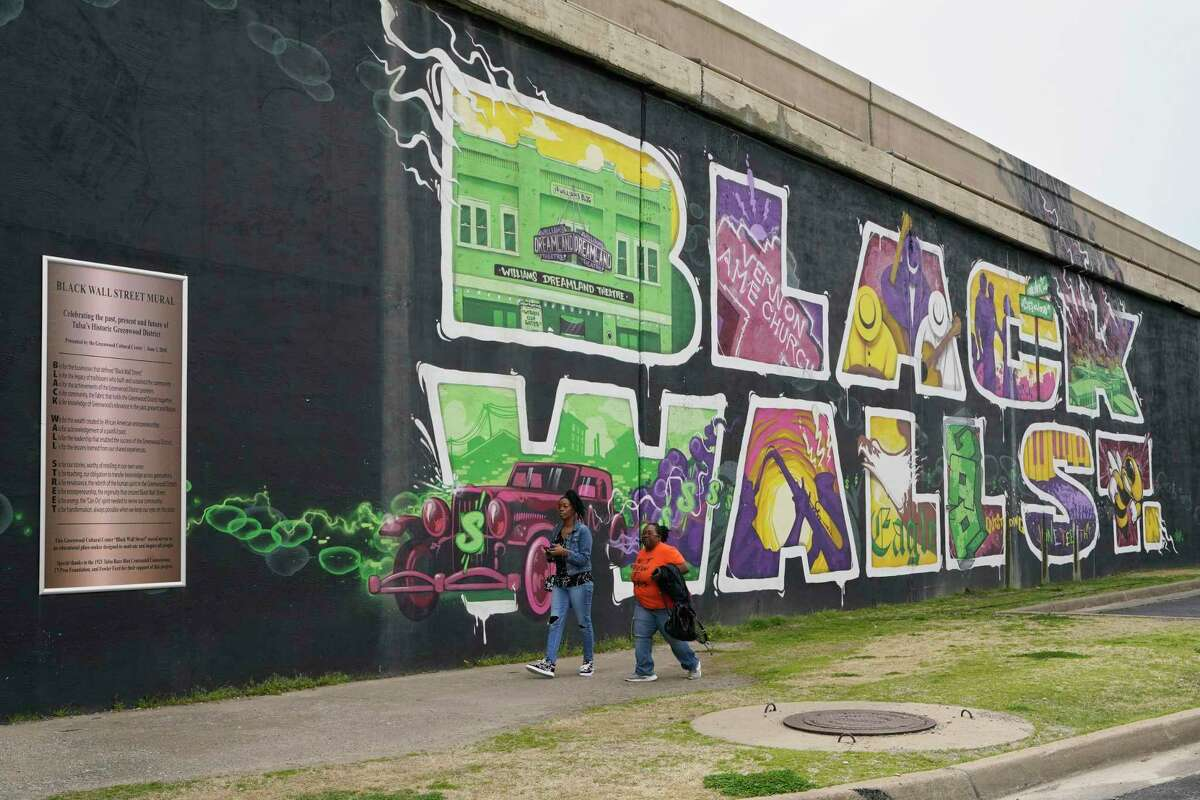 People walk past a mural commemorating Black Wall Street in Tulsa, Okla., in April. Artists and writers have been honoring the massacre, reviving history many had tried to erase.