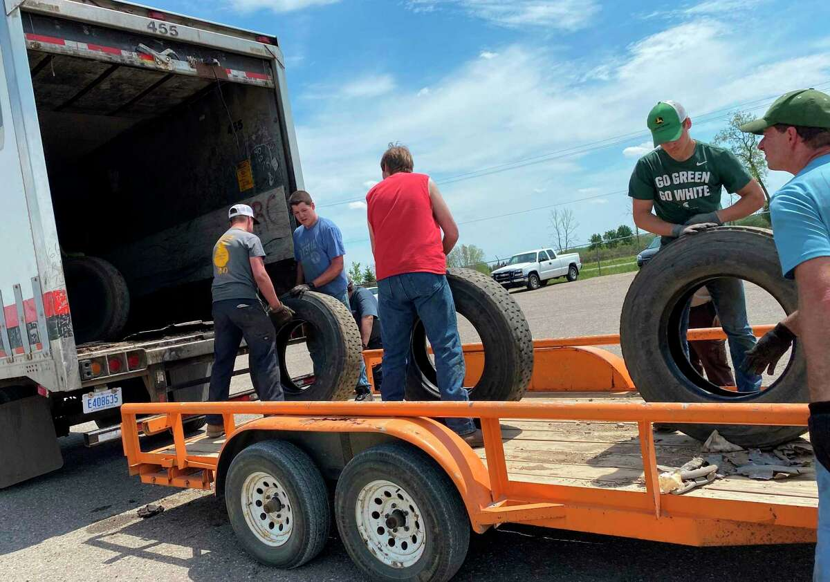 Volunteers load scrap tires into a trailer that will haul them off. (Courtesy Photo)