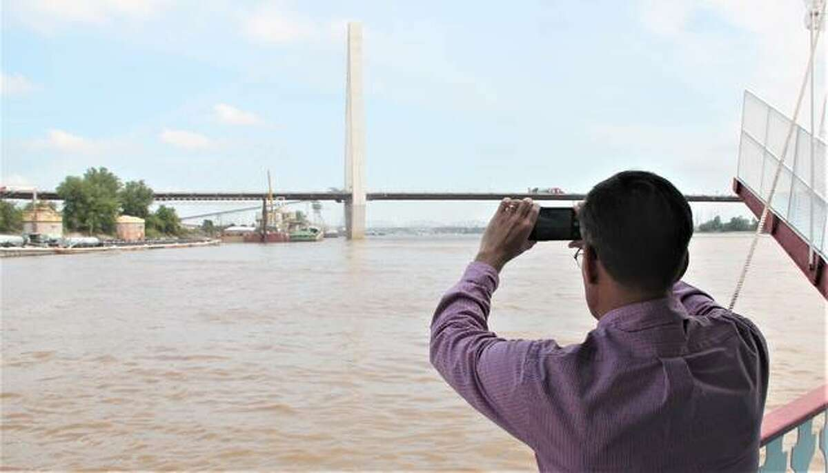 A participant on a riverboat cruise on the Tom Sawyer takes a photograph of one of the Mississippi River bridges and barging operations. The tour was one of the few live events of FreightWeekSTL2021, an annual industry conference sponsored in part by St. Louis Regional Freightway, an arm of Bi-State Development. The tour gave people a chance to see the industrial operations on the river, as well as infrastructure improvement.