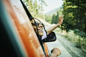 Smiling woman with head and hand out of car window enjoying view of mountains.