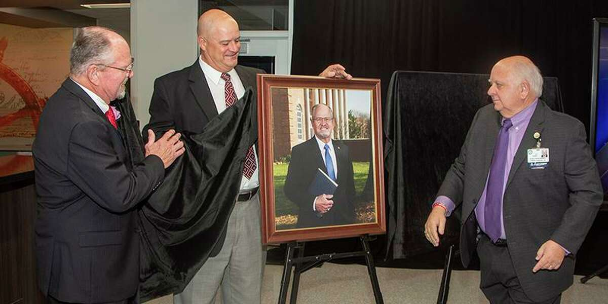 Leonard Brautigam's portrait is unveiled during the dedication ceremony on May 23. Joining Brautigam, left, to unveil the portrait are Dr. Mark Henry, CFISD superintendent of schools, middle, and Bob Covey, CFISD Board of Trustees president.