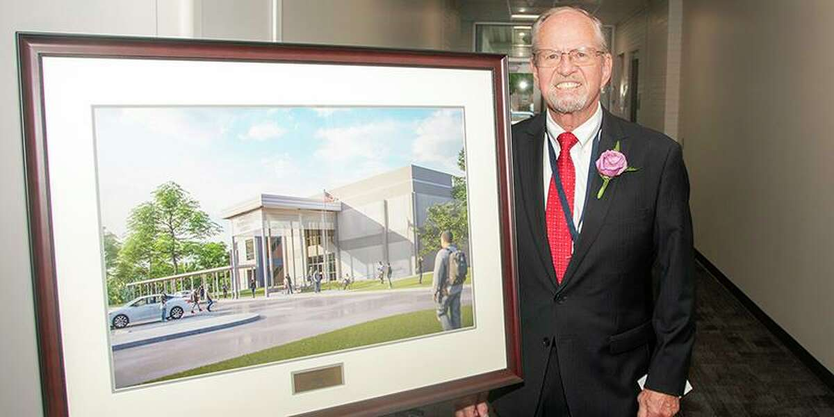 Leonard Brautigam, former assistant superintendent of student services, stands next to a portrait of the Brautigam Center during a dedication ceremony on May 23. The school was designed by PBK Architects Inc. and constructed by ICI Construction Inc.