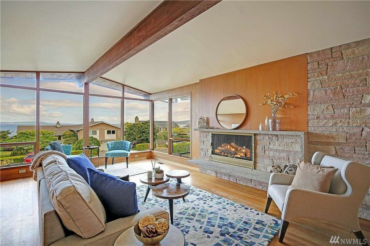 Inside, we see midcentury hallmarks: beamed ceilings; a large stone double-sided fire-place anchoring the wood paneled living room; and dining room on other side.