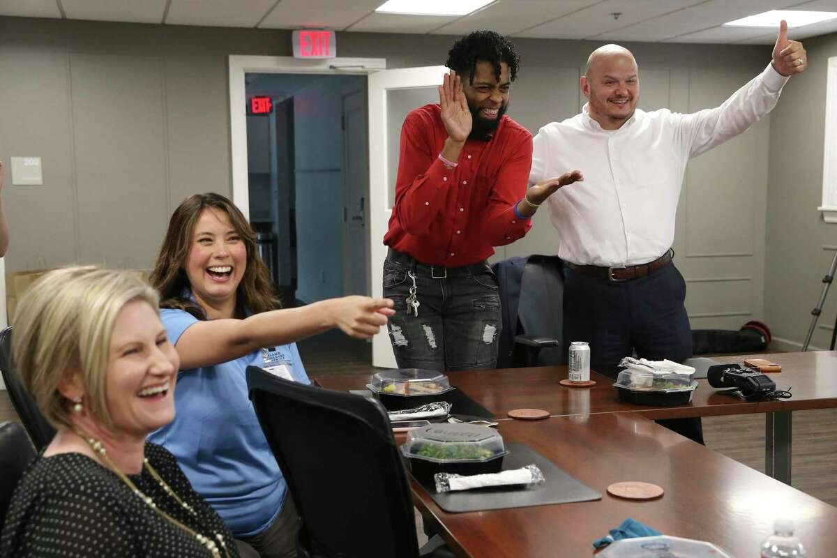 San Antonio College President Robert Vela, right, celebrates with 2021 graduate, Greg Torres and staff, Christi Horton, left, and Letty Adams, after being named the top community college in the U.S. by the Aspen Institute during an online presentation, Tuesday. The distinction reflects SAC's importance to the community.