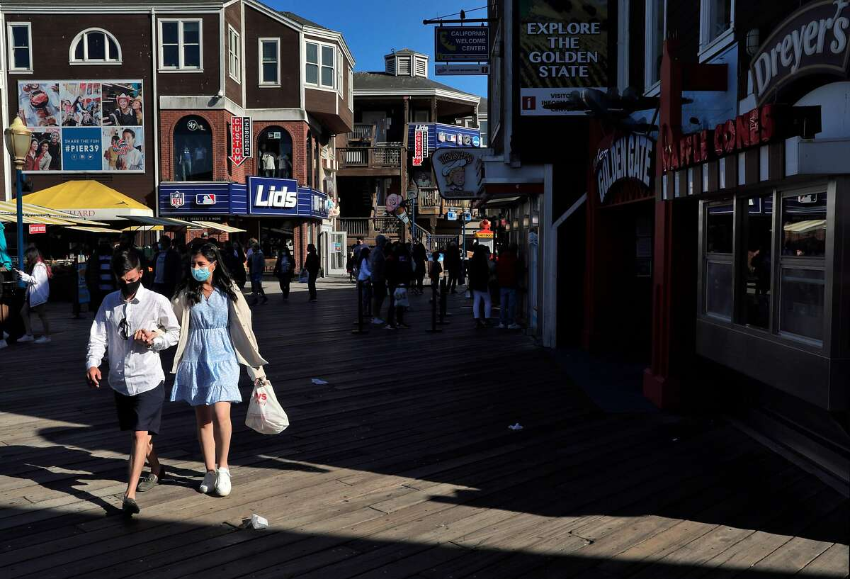 Ryan Berg and Maggie Levangie, of Boston, walk along Pier 39 while on vacation in San Francisco, Calif., on Monday, May 24, 2021. Tourism has begun to pick up again in San Francisco in advance of the travel season as the city's reopening has offered people the chance to visit with little fear of infection of COVID-19.