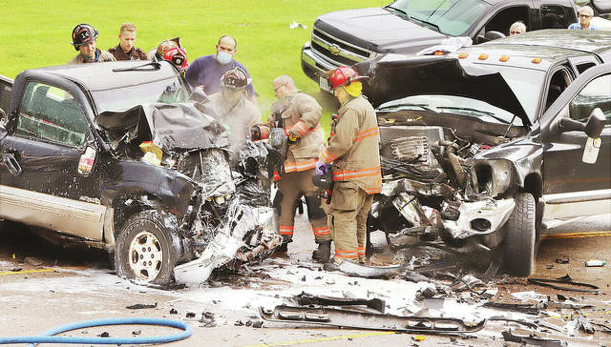 Godfrey firefighters use an hydraulic rescue tool on a full size Chevrolet pickup truck, left, Thursday to free the driver who was trapped after a head-on crash on Delmar Avenue at Emma Lane in Godfrey.