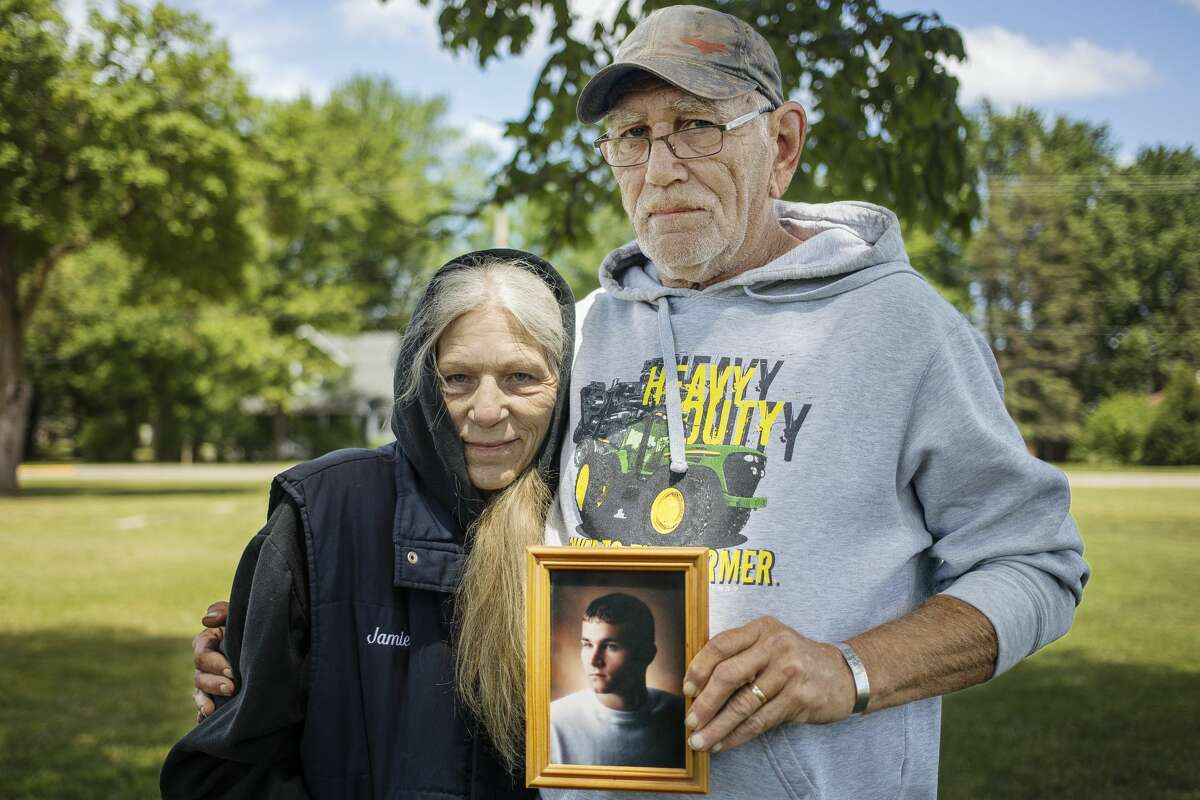 Jamie Zylman, left, and Randy Zylman, right, pose for a portrait Friday, May 28, 2021 with a photo of their late son, Army Cpl. Casey Zylman, who was killed in action May 25, 2007 while serving during Operation Iraqi Freedom. (Katy Kildee/kkildee@mdn.net)