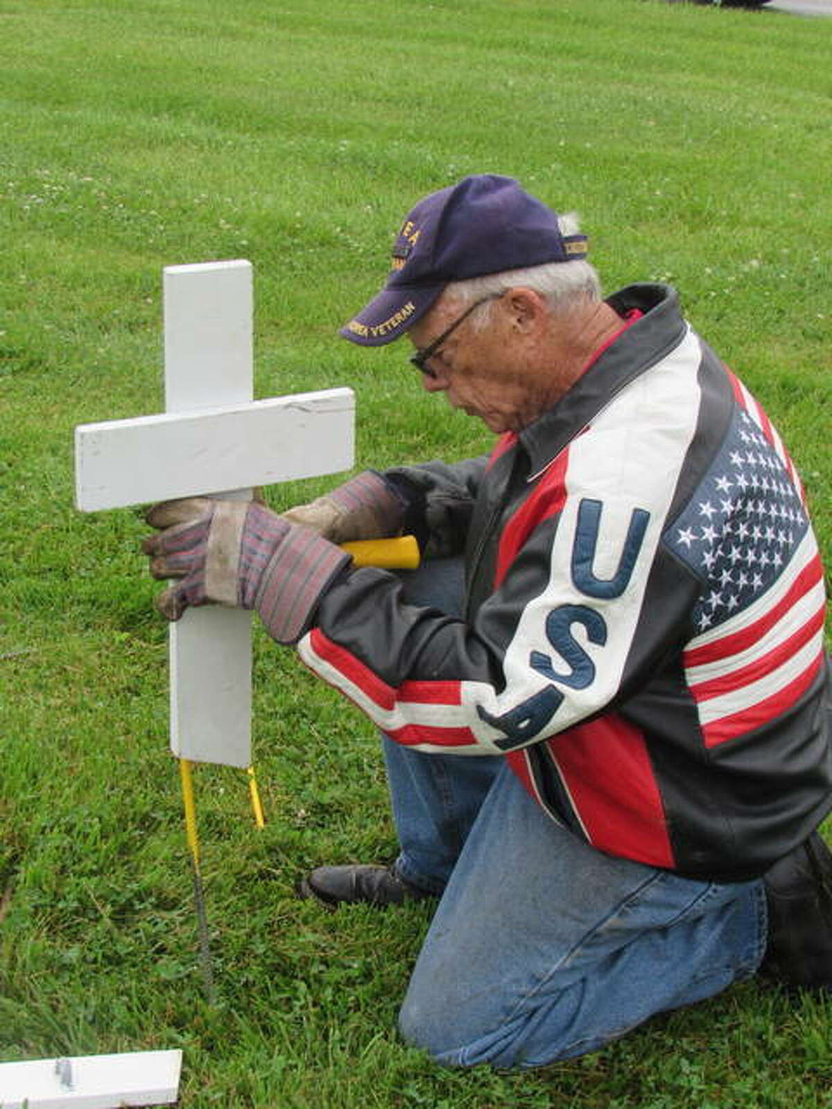 Fred Smith of Alton places miniture crosses at a Memorial Day display in Alton. He also created displays in Grafton and Bethalto.