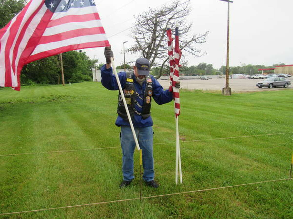 Bob Hillen sets flags in place Friday morning outside Farm & Home on Homer M. Adams Parkway in Alton.