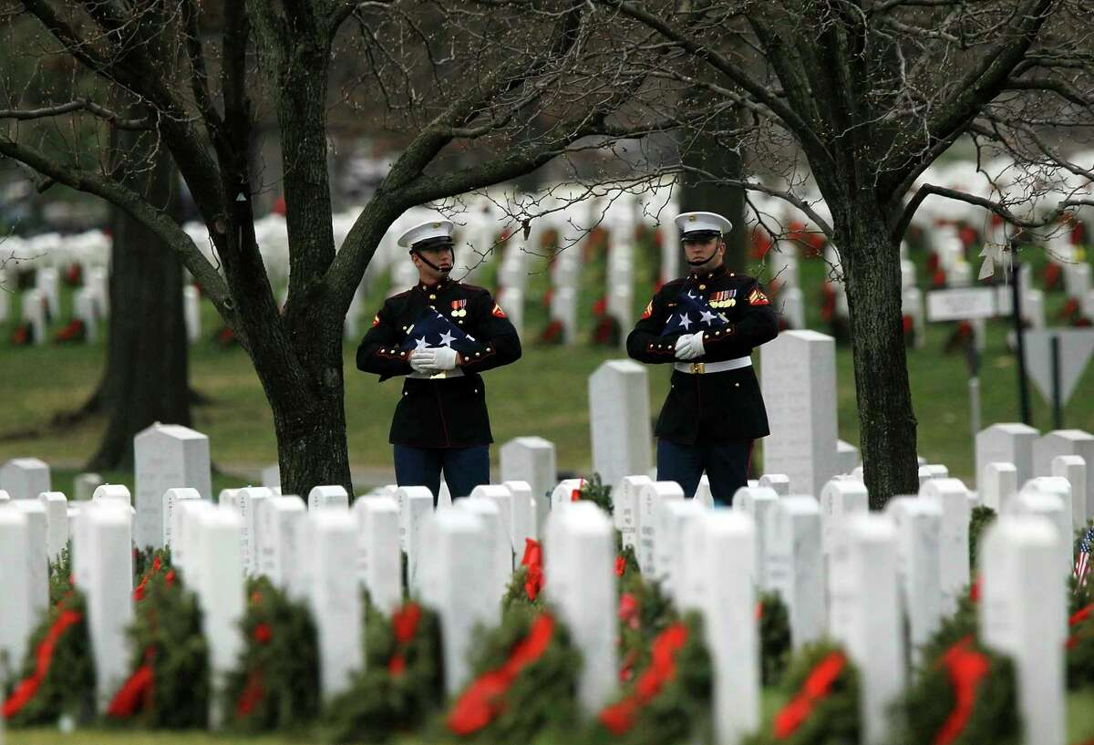 U.S. Marine Corps honor guards hold folded U.S. flags as they arrive at the funeral of a Marine Corps Staff Sergeant in 2011 at Arlington National Cemetery in Arlington, Virginia. (Alex Wong/Getty Images/TNS)