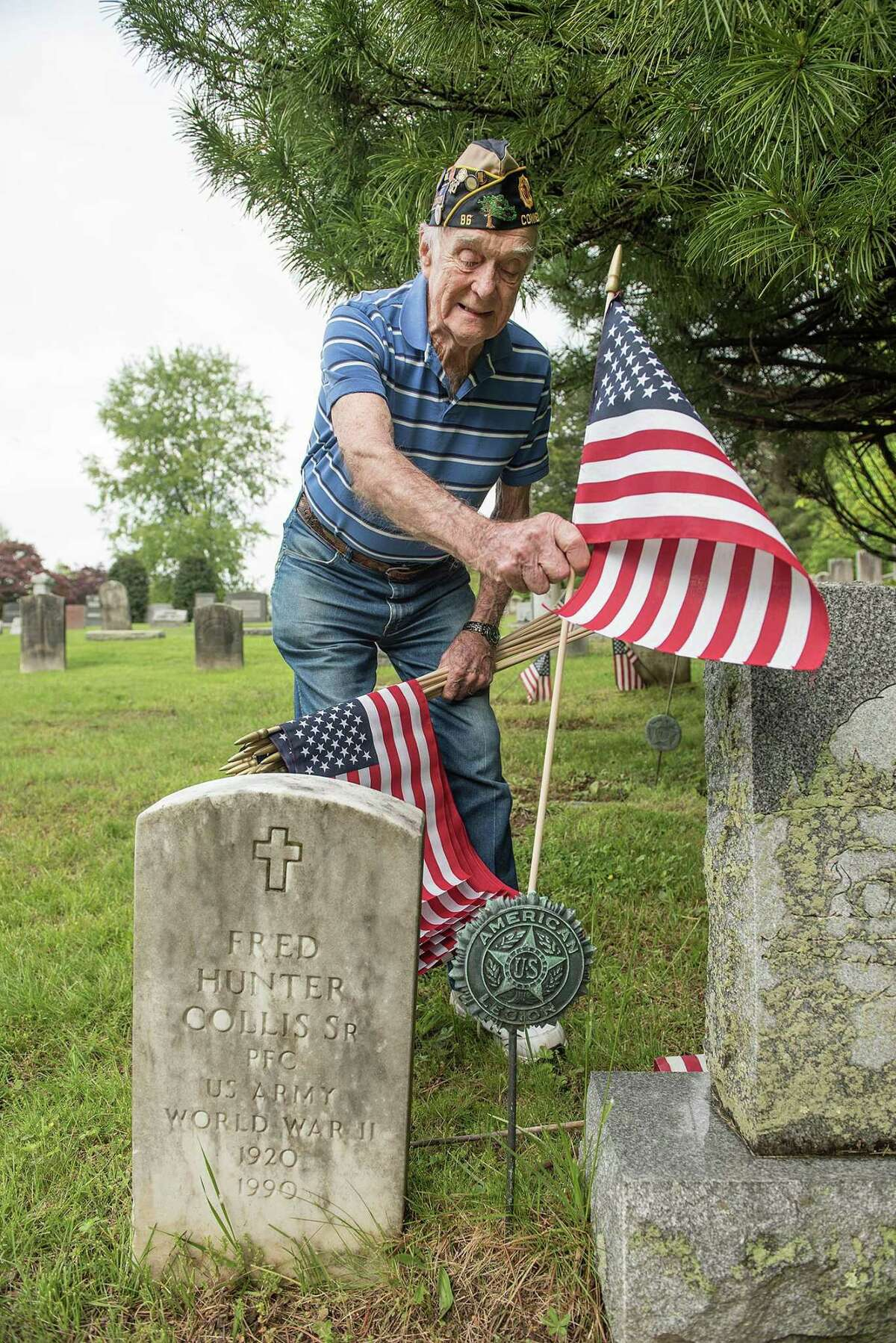 Air Force veteran Bing Ventres places a flag at the grave of Fred Hunter Collis Sr., at Hillside Cemetery in Wilton on May 20, 2019.