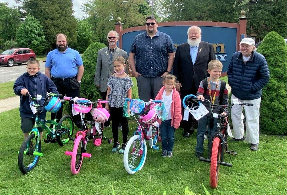Members of the Manistee Masonic Lodge No. 228 pose for a photo Friday with four Jefferson Elementary students who earned bicycles through the Bikes for Books program. (Courtesy photo)