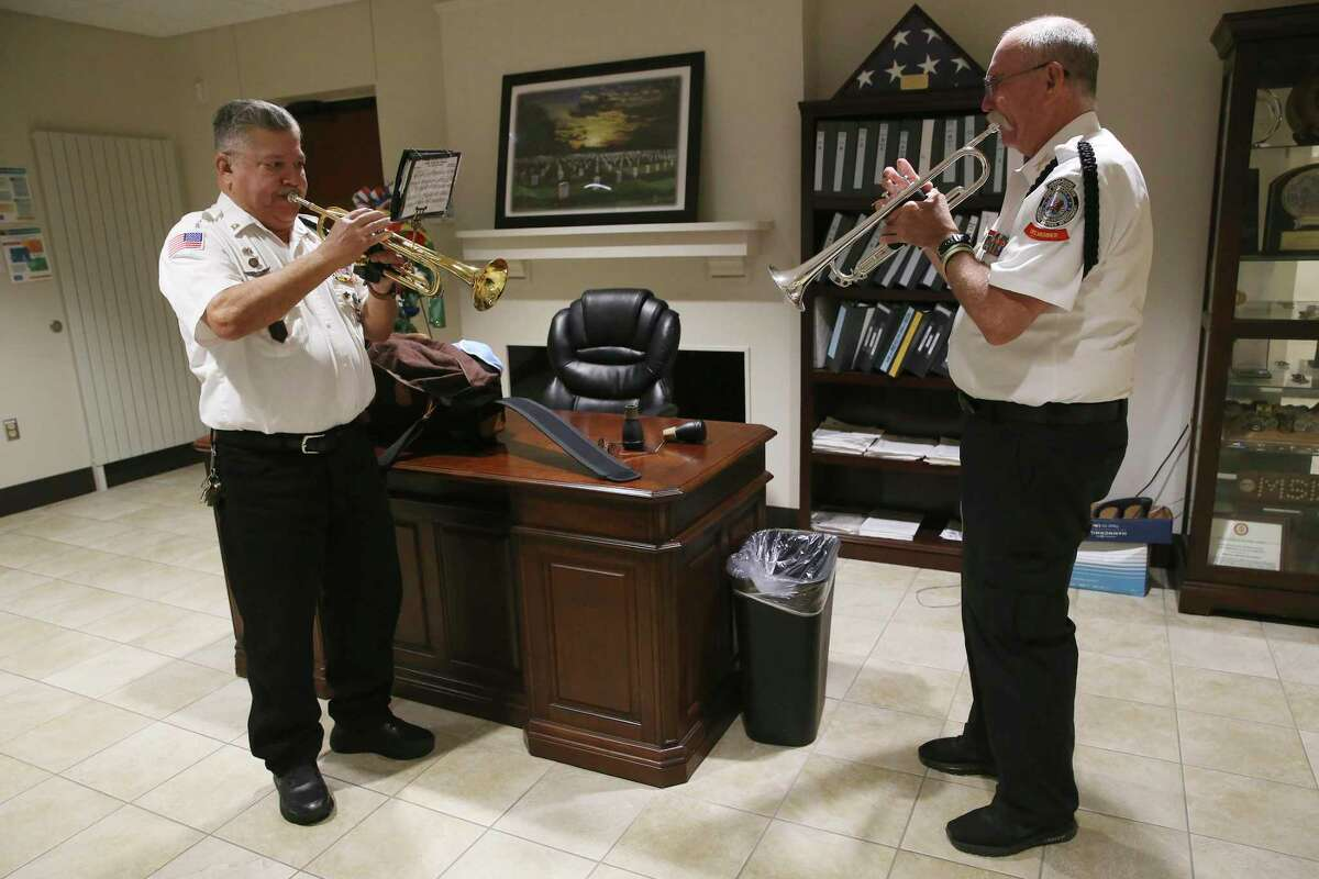 """Robert Ramirez, left, and Mike Kinkade, both 72, warm up before a day of services at Fort Sam Houston National Cemetery last week. They are among the seven buglers in the cemetery's all-volunteer detachment that provides final honors at funerals, including a live rendition of """"Taps."""""""