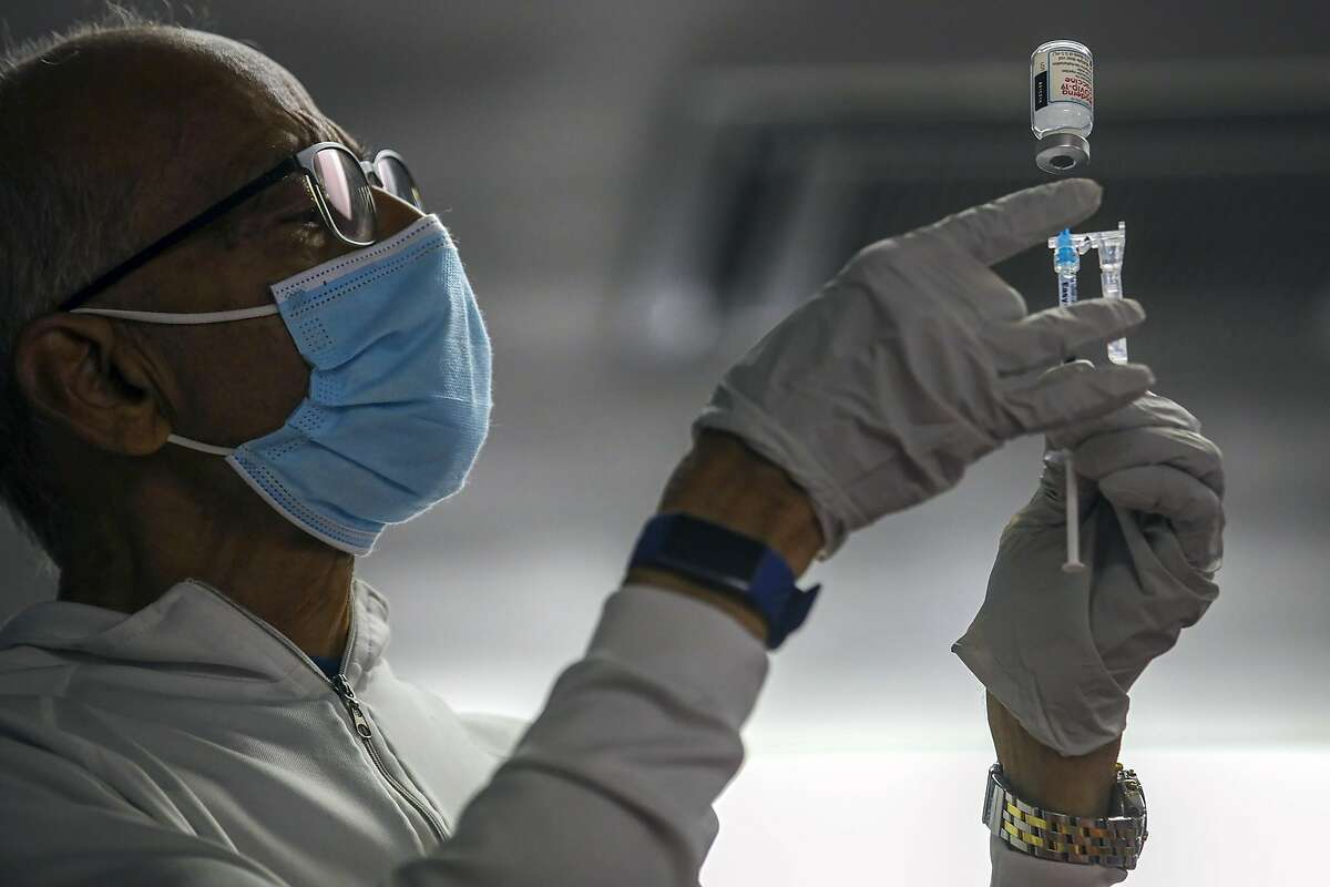 Dr. Narendra Parson prepares a COVID-19 vaccine at a clinic at Sanatan Dharma Temple in Norwalk, Calif., on May 8, 2021.