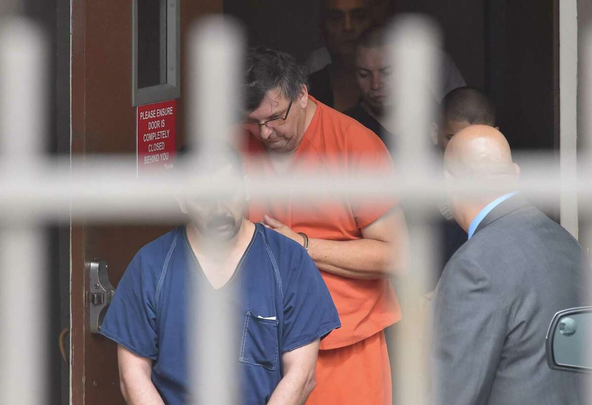 Ryan Glenn Martinez, seen in orange prison garb being led out of federal court in 2018, pleaded guilty Friday to conspiracy to commit bank fraud. He is scheduled to be sentenced in August.