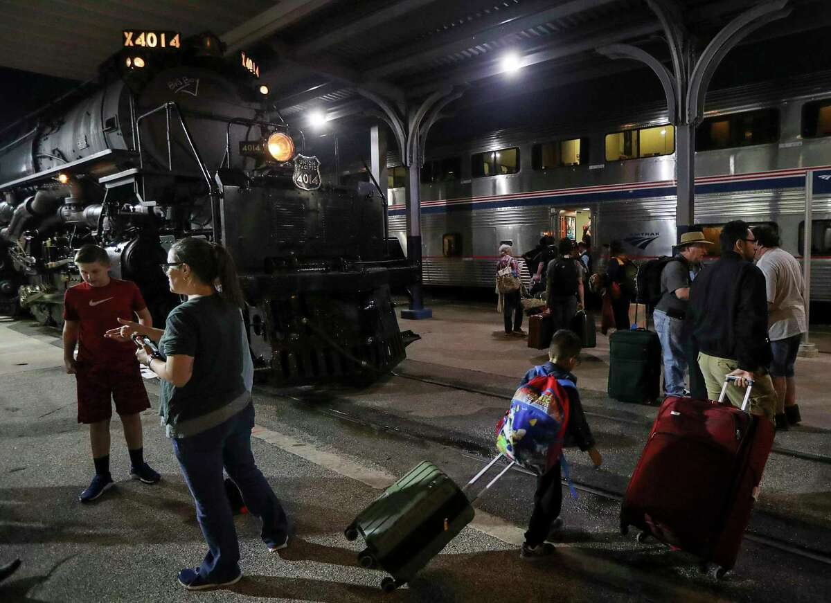 Amtrak passengers board a train as Union Pacific engine 4014, aka the Big Boy, sits at the Houston station on Nov. 6, 2019.
