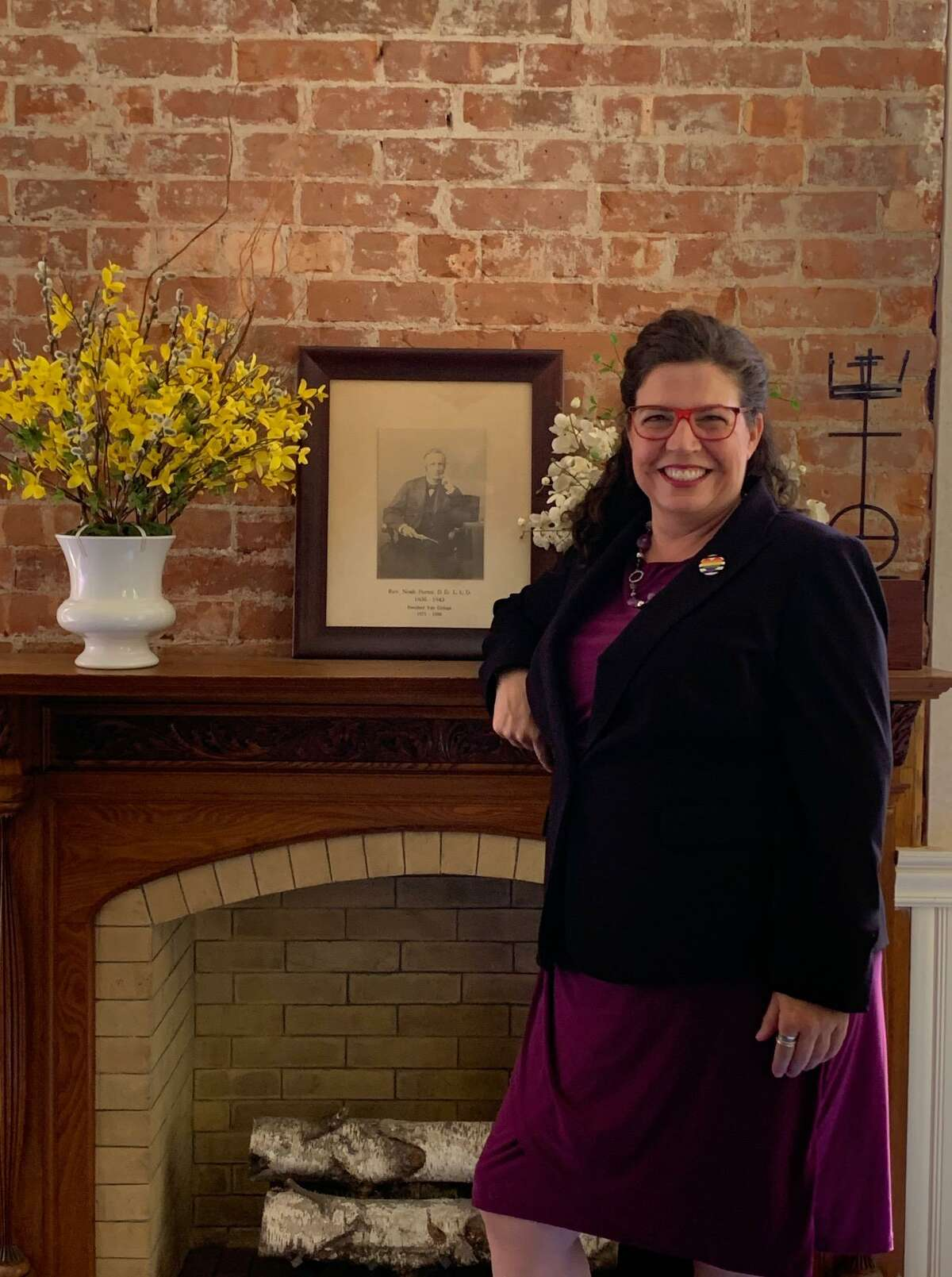 Amy Carter, standing beside a photograph of the Rev. Noah Porter, who served from 1836 to 1843.