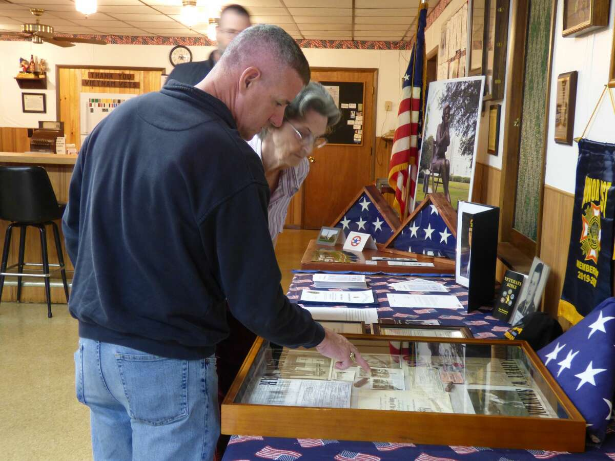 Marla Sexton presents Kaleva VFW post commander Sean Knudsen with a shadowbox memorial containing items from her late husband's service with the U.S. Armed Forces.