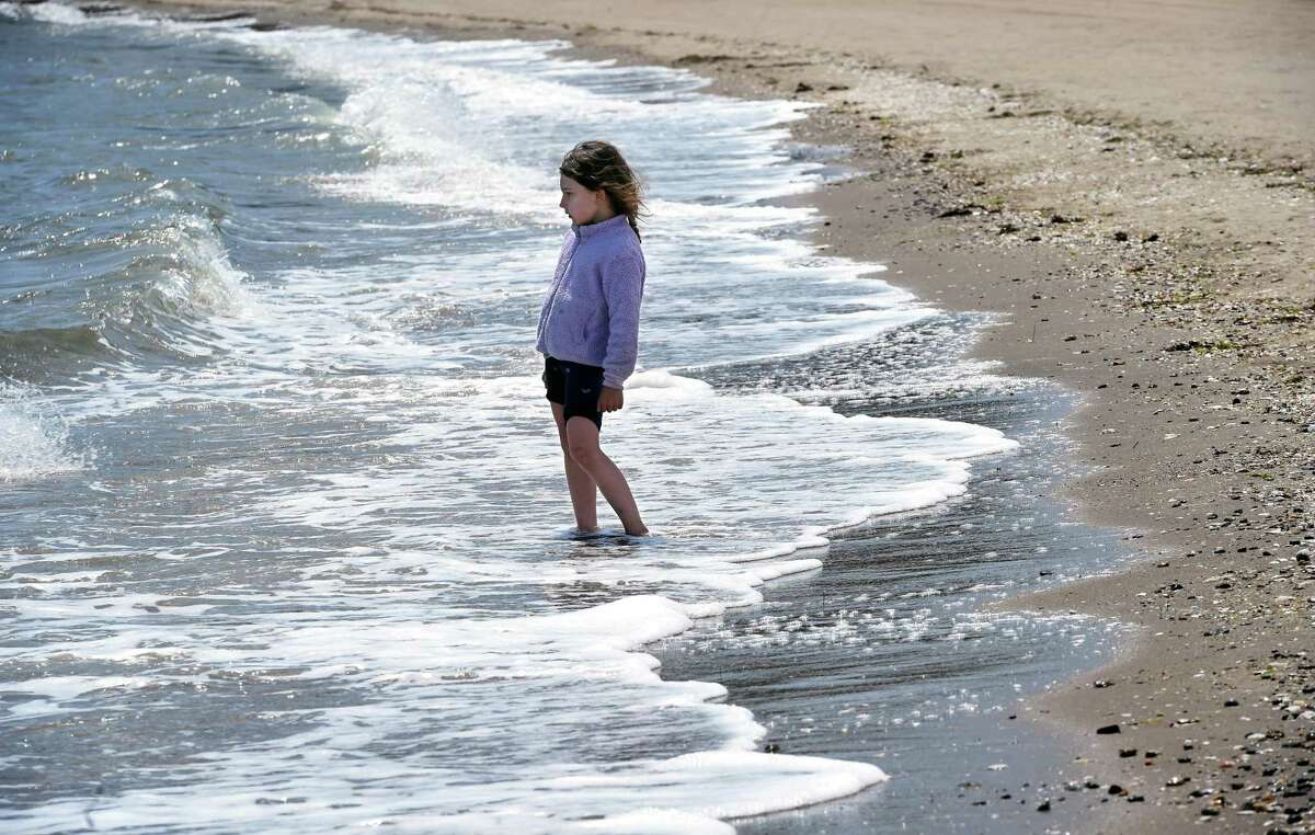 Bellamy Wallengren, 5, of New Preston lets the waves wash over her feet at Jacob's Beach in Guilford on May 28, 2021.