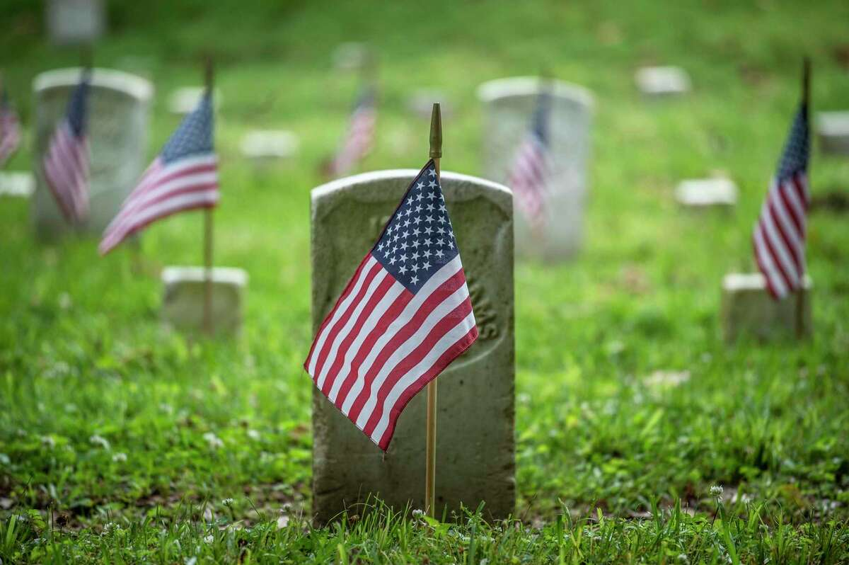 Flags are placed near headstones at the Vicksburg National Cemetery during the Memorial Day flag placement event in Vicksburg, Miss., Friday, May 28, 2021. About 40 volunteers placed nearly 1,700 flags. (Eric Shelton/The Clarion-Ledger via AP)