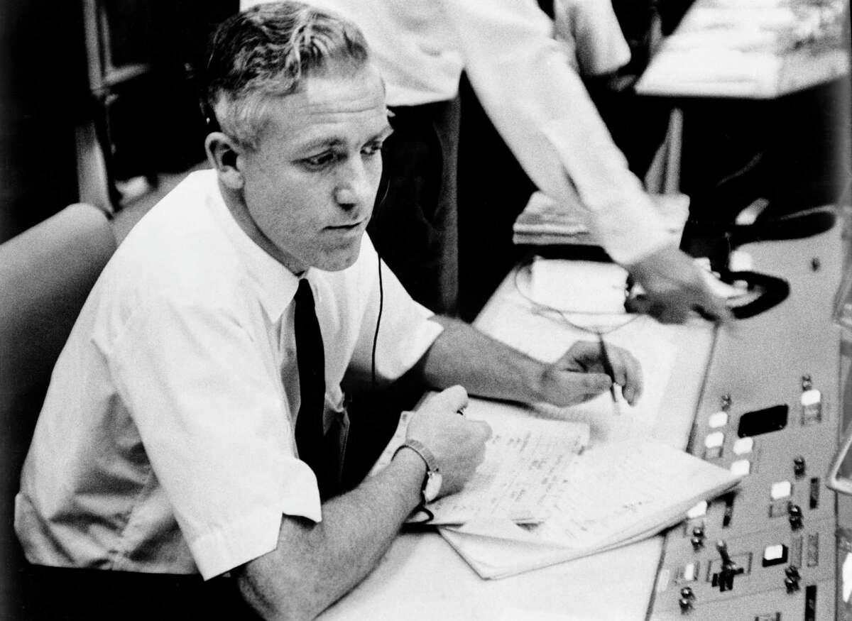 John Hodge is shown at his console during a training exercise ahead of the Gemini 4 mission.