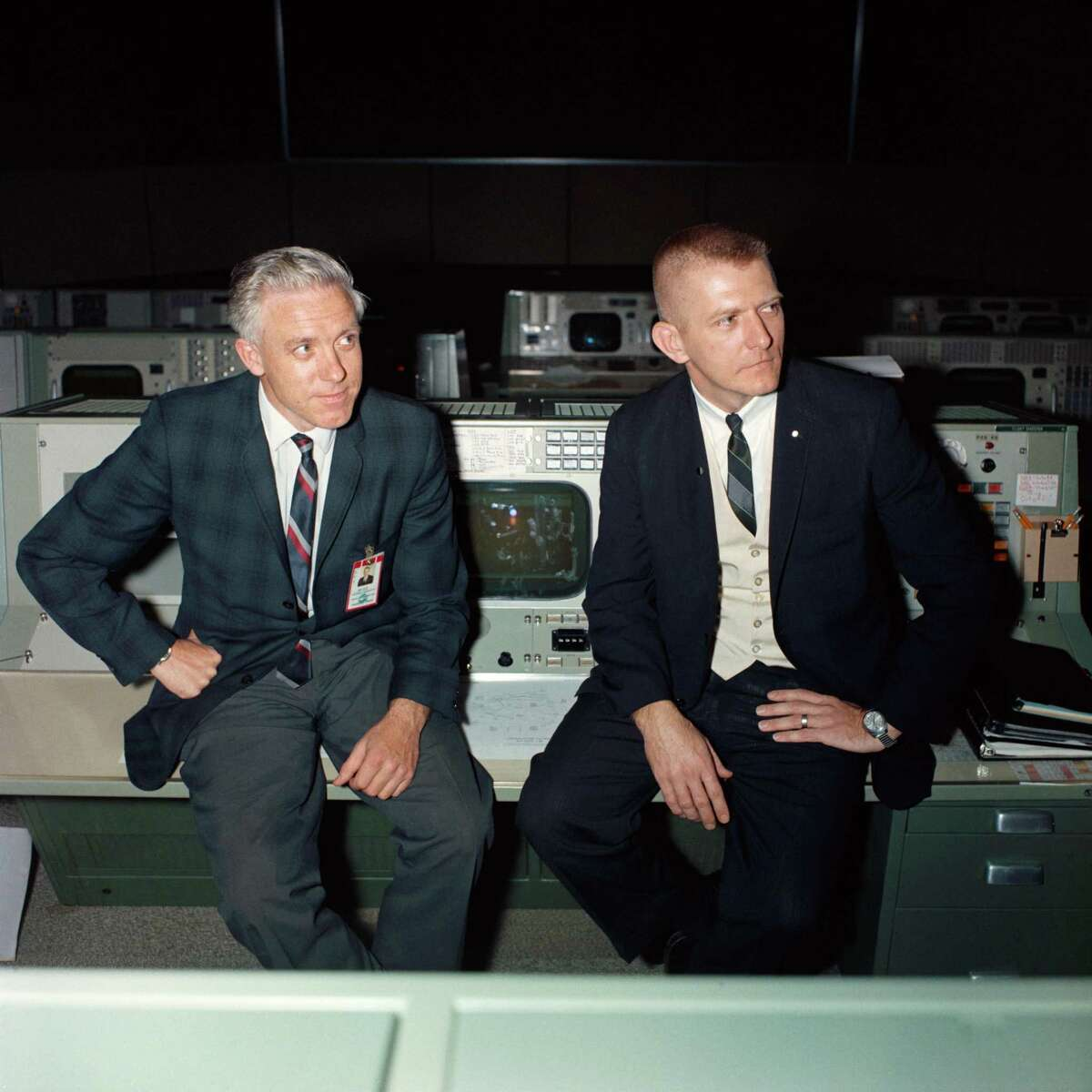 John Hodge, left, and Gene Kranz are seated on the Flight Directors console in the 3rd floor Mission Control Center following the Apollo 5 test flight.