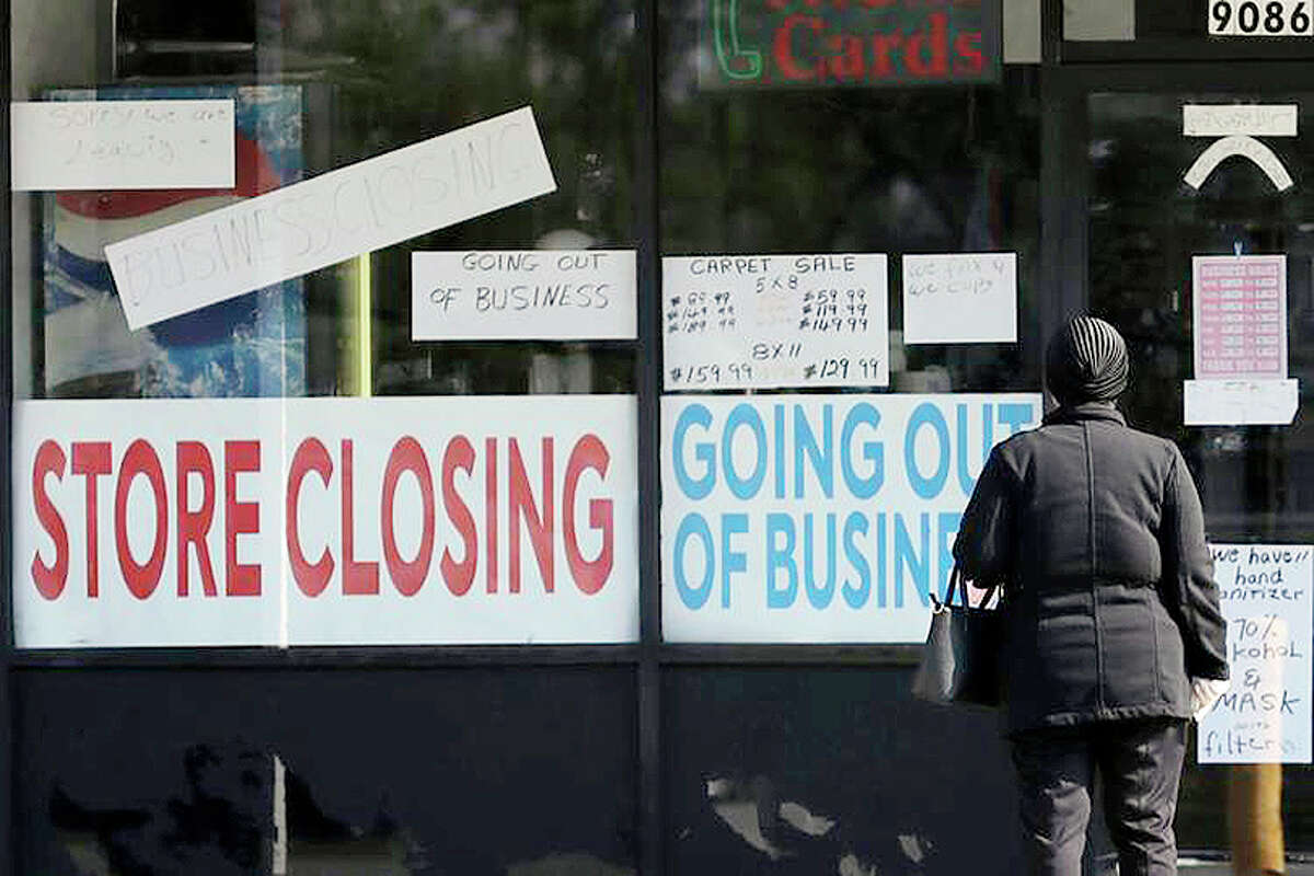 A woman looks at signs at a Niles store closed by COVID-19.