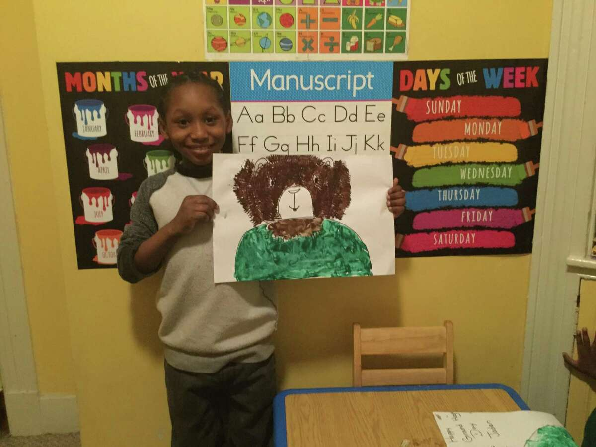 A child presents artwork at Babe's Day Care in New Haven.