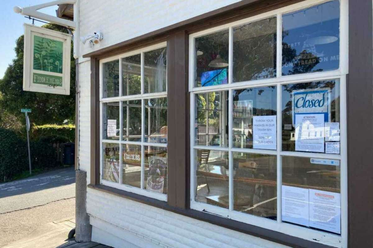 A Mendocino cafe owner who last year shut down his restaurant instead of requiring workers to wear face masks is now asking that any customer wearing a mask pay a $5 fee.