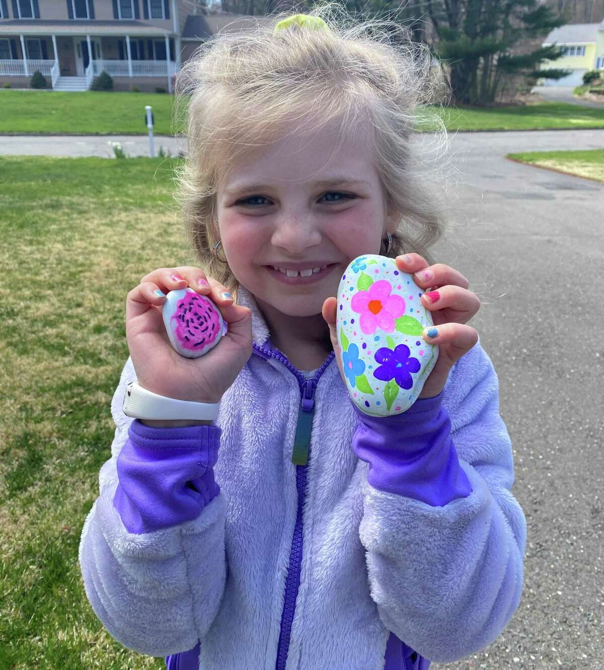 Ava DeMartino shows off a pair of Trumbull Rocks! before setting off the hide them around town.